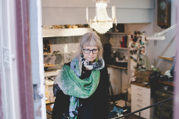 Senior female owner wearing scarf in jewelry store