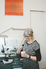 Senior woman smiling while holding coffee cup in jewelry workshop