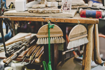 Whisk brooms hanging from workbench in jewelry workshop