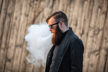 Vape man. Outdoor portrait of a young brutal white guy with large beard and in sunglasses letting puffs out of steam from an electronic cigarette opposite the old wooden fence in the village. Vaping.