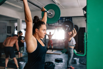Muscular woman exercising with barbell in a gym
