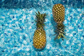In the pool on the water two pineapples float. Tropical fruits, healthy food, summer, top view