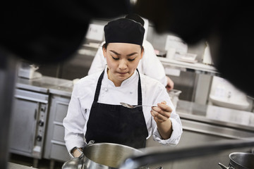 Young female chef tasting food from cooking pan at commercial kitchen
