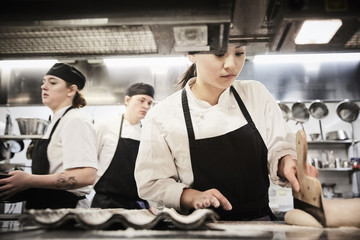 Female chef student cutting dough in commercial kitchen