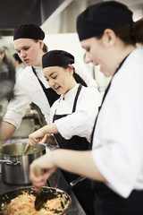 Male and female chefs cooking food in kitchen at restaurant