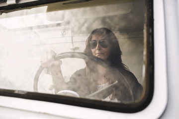 Businesswoman wearing sunglasses while driving portable office truck