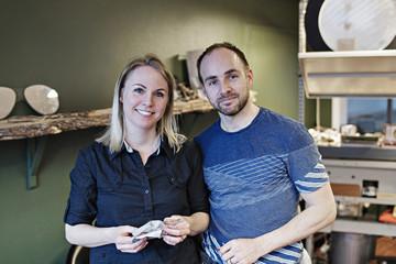 Portrait of confident couple standing in eyeglasses workshop