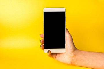 Woman hand holding modern smartphone in hand on yellow background.