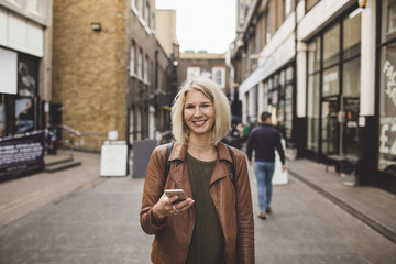 Portrait of smiling young woman holding mobile phone on road in city