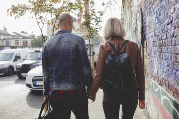 Rear view of couple holding hands while walking on sidewalk in city