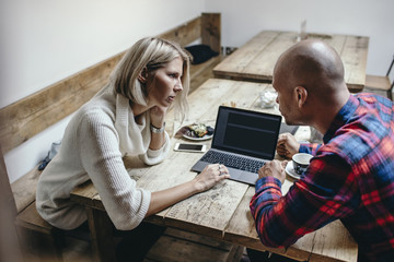 Multi-ethnic couple discussing while using laptop at table in coffee shop