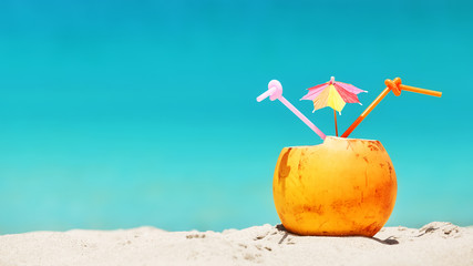 Coconut with straws and colorful cocktail umbrella on a tropical beach, summer holiday concept, selective focus, space for text.