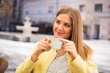 Beautiful young woman enjoys drinking coffee at the city.
