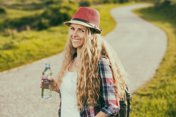 Beautiful young woman drinking water while resting from walking at the country road.