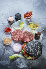 Raw burgers made of ground beef meat, black hamburger and cooking components, vertical shot on a grey stone surface