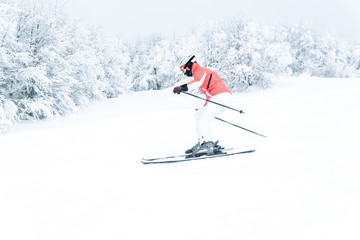 Woman skier skiing fast downhill