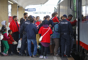 Austrian policemen watch as migrants take a train towards Germany from the Wien Westbahnhof railway station in Vienna