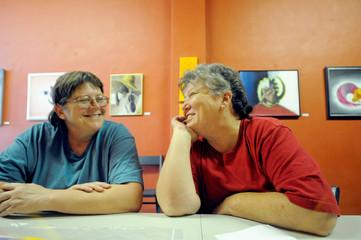 Cheryle Rudd (L) and Kitty Lambert sit in Lambert's art gallery in Buffalo