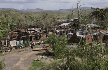 A man walks past damaged homes in the aftermath of Hurricane Patricia in the town of Chamela near Punto Perula, in the Mexican state of Colima