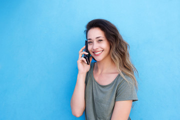 smiling young woman talking on cellphone against blue wall