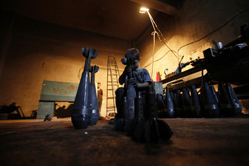 Issa assembles a locally handmade mortar shell in a weapons factory of the Free Syrian Army in Aleppo