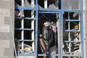 Vendor steps out of his shop damaged by a Saudi-led air strike in Yemen's capital Sanaa