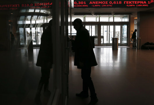A man is silhouetted at the Athens Stock Exchange reception hall as an electronic board displays stock prices