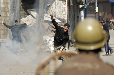 Kashmiri protester throws piece of brick towards Indian policeman during anti-Indian protest in Srinagar