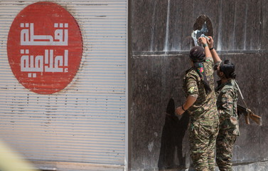 YPG fighters remove an Islamic State sticker in Tel Abyad