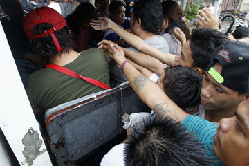 Survivors reach out to receive medicine from passing vehicle along devastated downtown after super Typhoon Haiyan battered Tacloban city