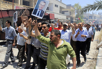 Civilians hold up pictures of Bashar al-Assad and of Hafez al-Assad as they celebrate in Qusair