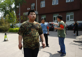 Men guard the entrance of building G at Chaoyang Hospital, where blind activist Chen was reported to be staying at, in Beijing