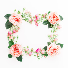 Frame made of purple roses, leaves and pink buds on white background. Flat lay, top view. Floral composition of pink flowers