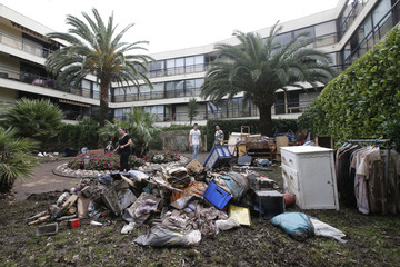 Water-damaged personal belongings and furniture are stacked outside a residential apartment building the day after torrential rains caused flooding in Mandelieu-La Napoule