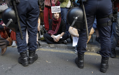 """A supporter of the grassroots """"Indignados"""" movement with a placard on her forehead stages a protest in front of a Bankia bank branch near Madrid's Puerta del Sol"""