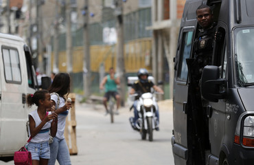 School children eat ice cream as a policeman takes position during an operation in the Mare slums complex in Rio de Janeiro