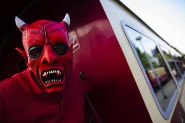 Man with devil make-up poses for a picture on railway carriage travelling through Harz mountains during