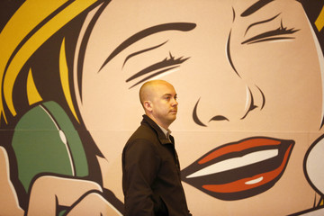 A man walks past a stand advertising printed wall paper at the 100% Design exhibition at Earl's Court in London