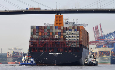 """Towboats tow the container ship """"Hamburg Express"""" as it passes below  the Koehlbrand bridge during its arrival near the Port of Hamburg"""