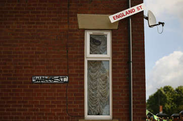 A temporary road sign hangs from a drain pipe on Wales Street in Oldham