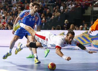 Denmark's Noddesbo falls as Croatia's Kopljar looks on during their Men's Handball World Championship semi-final match in Barcelona