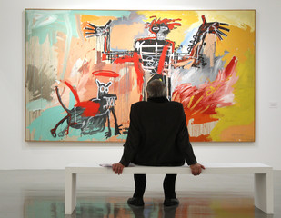 "A visitor looks at the painting ""Boy and Dog in a Johnnypump, 1982"" before the opening of the exhibition ""Basquiat"" at the Museum of Modern Art in Paris"