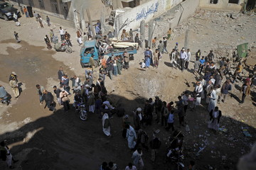 People move furniture from a house damaged by a Saudi-led air strike in the neighbourhood of Al-Garda at Shomila area in Yemen's capital Sanaa