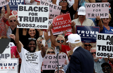 Republican U.S. presidential nominee Donald Trump looks back at supporters holding signs at a campaign rally in Lakeland
