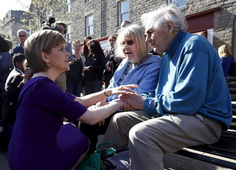 Scottish National Party (SNP) leader Sturgeon talks to a couple during a campaign visit to Portobello, Scotland