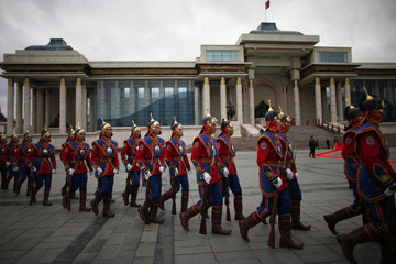 Members of the Mongolian State Palace honour guards arrive before an official welcoming ceremony for visiting German Chancellor Merkel in Ulan Bator