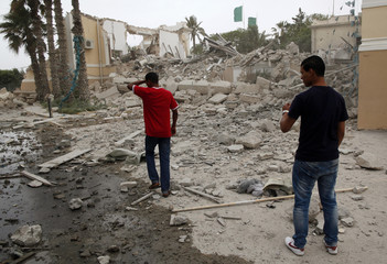 Youths shield their faces from the dust as they pass a government building damaged by coalition air strikes in Tripoli