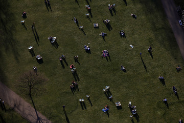 An aerial view shows people sitting in a Park in London