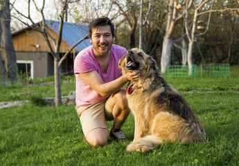 Handsome asian man stroking his fluffy dog on a sunny day in a garden.