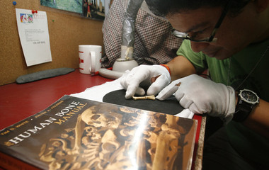 University of the Philippines Professor Armand Mijares, an archaeologist, displays a 67,000-year-old foot bone at his office in Quezon City